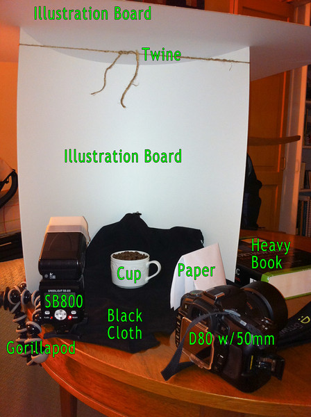 """<a href=""""http://www.jawsnap.net/Daily/year3/11272102_ACXDJ#1007081269_ZeGZ3"""">2010-09-13 Dainty Coffee</a> SETUP The heavy book, Gorillapod and twine keeps the bottom illustration board bent in a half circle so the other illustration board can just sit on top. The paper was necessary to fill in a darker part of the cup that wasn't getting enough light."""