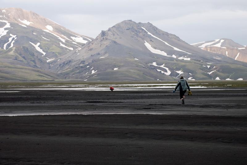 Þorbjörg skolar skónna. Álfhildur á leið til hennar.