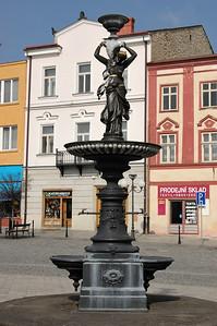 Kašna se sochou Hygie na náměstí v Příboře. Umělecký odlitek, šedá litina.