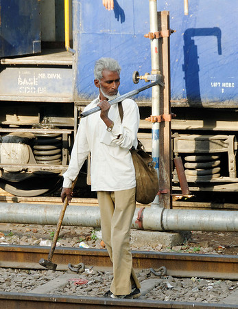 This gentleman was the rail quality control inspector.  That's a wrench with a cheater bar on his shoulder.  He would rap the rails looking for loose bolts.  We boarded the train anyway. Agra Railway Station