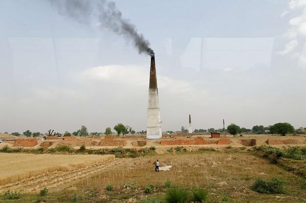 Brick kilns belching smoke dot the landscape, road to Agra