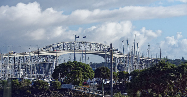 "The Auckland Harbor Bridge with its ""Nipon Clipons,"" two side strutures built in Japan added to each side to give more lanes to the bridge"