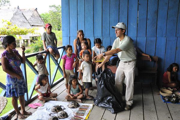 Robinson shows the kids the books and materials our group brought them, Libertad, Rio Ucayali, Peru