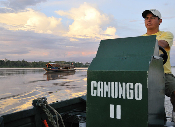 Our launch headed home with a local craft at sunset, Canal de Puinahua, Peru