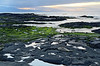 Isla Santiago sunset, fur seal and intertidal pools - the small bumps in the water are marine iguanas