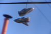 """Shoes hanging from power lines in Costa Rica is known as """"shoefiti.""""  Possible explanations are modern art, good way of getting rid of old shoes, marking territory (drugs, etc.), memorial to someone - take your choice."""