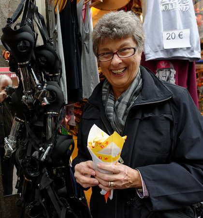 Amsterdam; and here's some of the fast food; Suzanne with fries and mayo.  Notice the bong masks hanging beside her