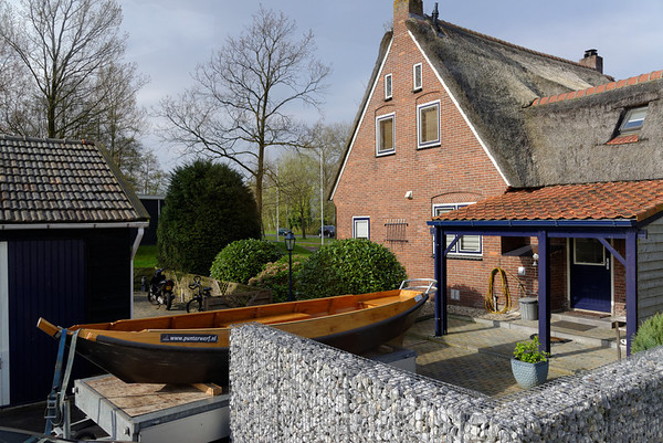 Giethoorn; wooden boat, note loose rock wall