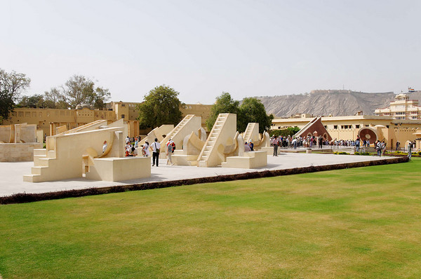 Jantar Mantar, Jaipur.  The observatory consists of fourteen major geometric devices for measuring time, predicting eclipses, tracking stars' location as the earth orbits around the sun, ascertaining the declinations of planets, and determining the celestial altitudes and related ephemerides. Each is a fixed and 'focused' tool. The Samrat Yantra, the largest instrument, is 90 feet high, its shadow carefully plotted to tell the time of day. Its face is angled at 27 degrees, the latitude of Jaipur. The Hindu chhatri (small cupola) on top is used as a platform for announcing eclipses and the arrival of monsoons. Built from local stone and marble, each instrument carries an astronomical scale, generally marked on the marble inner lining. Bronze tablets, all extraordinarily accurate, were also employed. Thoroughly restored in 1901, the Jantar Mantar was declared a national monument in 1948.