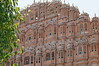 """Hawa Mahal (""""Palace of Winds"""" or """"Palace of the Breeze""""), is a palace in Jaipur, India. It was built in 1799 by Maharaja Sawai Pratap Singh, and designed by Lal Chand Usta in the form of the crown of Krishna, the Hindu god. Its unique five-storey exterior is also akin to the honeycomb of the beehive with its 953 small windows called jharokhas that are decorated with intricate lattice work.  The original intention of the lattice was to allow royal ladies to observe everyday life in the street below without being seen, since they had to observe strict """"purdah"""" (face cover).  Built of red and pink sandstone, the palace is situated on the main thoroughfare in the heart of Jaipur's business centre. It forms part of the City Palace, and extends to the Zenana or women's chambers, the chambers of the harem."""