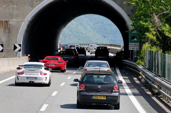 Ferrari and Porche racing ahead of bus