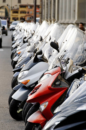 Florence, Italy; row of motorbikes along the Arno