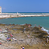 Trani, beachgoers on rocky beach with Cathedral of St.Nicholas in background