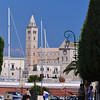 Trani, trimmed trees lining seaside park with the harbor and Cathedral of St. Nicholas in background