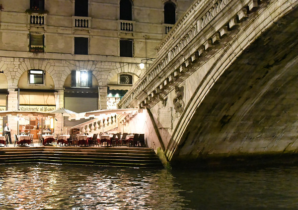 Venice; night cruise by water bus, empty tables by the Realto bridge