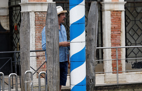 Venice; photographer hiding behind posts