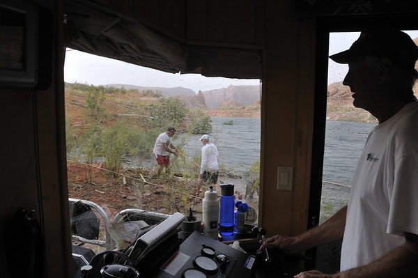 Storm hits.  Rich runs the engines to keep the stern from drifting as Earl and Frank secure the lines..