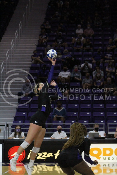 jumping into the air, the player sets the ball during the K-State volleyball game against Iowa State at Bramlage Coliseum on Sept. 25, 2020.