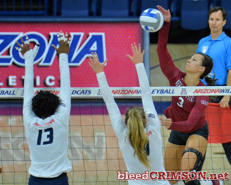 TUCSON, AZ - SEPTEMBER 15:  Jordan Abalos #3 of the New Mexico State Aggies takes a swing against the block attempt of Devyn Cross #13 and Julia Patterson #4 of the Arizona Wildcats in a match between the New Mexico State Aggies and the Arizona Wildcats at the McKale Center in Tucson, Arizona. The Wildcats won 3-2.  (Photo by Sam Wasson)