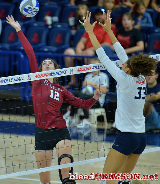 TUCSON, AZ - SEPTEMBER 15:  Megan Hart #12 of the New Mexico State Aggies takes a swing against Jade Turner #33 of the Arizona Wildcats in a match between the New Mexico State Aggies and the Arizona Wildcats at the McKale Center in Tucson, Arizona. The Wildcats won 3-2.  (Photo by Sam Wasson)
