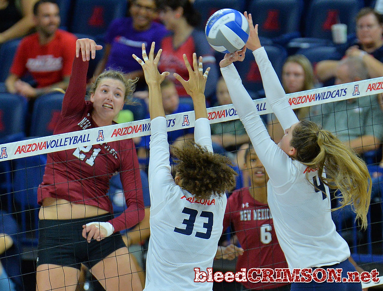 TUCSON, AZ - SEPTEMBER 15:  Lia Mosher #21 of the New Mexico State Aggies hits the ball through the block attempt of Jade Turner #33 and Julia Patterson #4 of the Arizona Wildcats in a match between the New Mexico State Aggies and the Arizona Wildcats at the McKale Center in Tucson, Arizona. The Wildcats won 3-2.  (Photo by Sam Wasson)