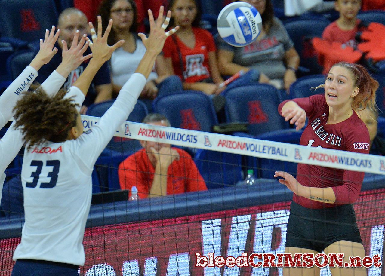 TUCSON, AZ - SEPTEMBER 15:  Kassandra Tohm #14 of the New Mexico State Aggies hits a ball past the block attempt of Jade Turner #33 of the Arizona Wildcats in a match between the New Mexico State Aggies and the Arizona Wildcats at the McKale Center in Tucson, Arizona. The Wildcats won 3-2.  (Photo by Sam Wasson)