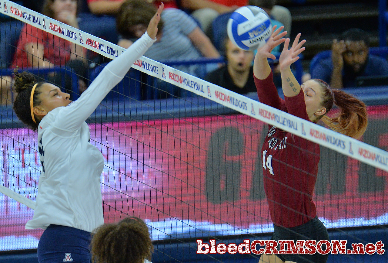 TUCSON, AZ - SEPTEMBER 15:  Kassandra Tohm #14 of the New Mexico State Aggies goes up for a block against Tyler Spriggs #35 of the Arizona Wildcats in a match between the New Mexico State Aggies and the Arizona Wildcats at the McKale Center in Tucson, Arizona. The Wildcats won 3-2.  (Photo by Sam Wasson)
