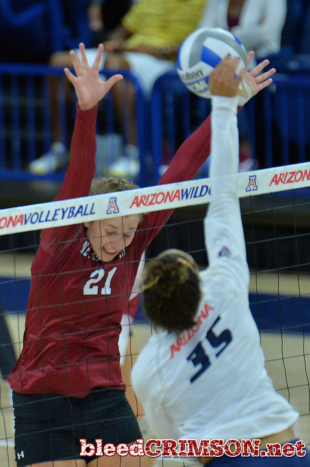 TUCSON, AZ - SEPTEMBER 15:  Lia Mosher #21 of the New Mexico State Aggies goes up for a block attempt against Tyler Spriggs #35 of the Arizona Wildcats in a match between the New Mexico State Aggies and the Arizona Wildcats at the McKale Center in Tucson, Arizona. The Wildcats won 3-2.  (Photo by Sam Wasson)