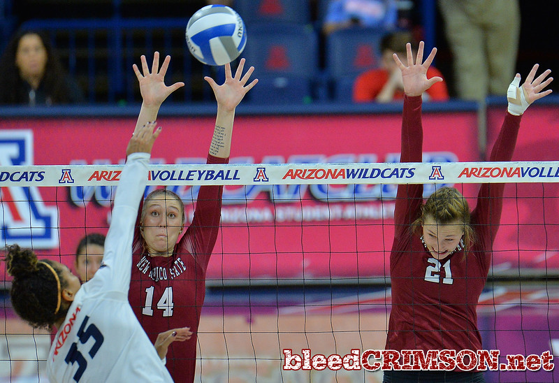 TUCSON, AZ - SEPTEMBER 15:  Kassandra Tohm #14 and Lia Mosher #21 of the New Mexico State Aggies go up for a block attempt against Tyler Spriggs #35 of the Arizona Wildcats in a match between the New Mexico State Aggies and the Arizona Wildcats at the McKale Center in Tucson, Arizona. The Wildcats won 3-2.  (Photo by Sam Wasson)
