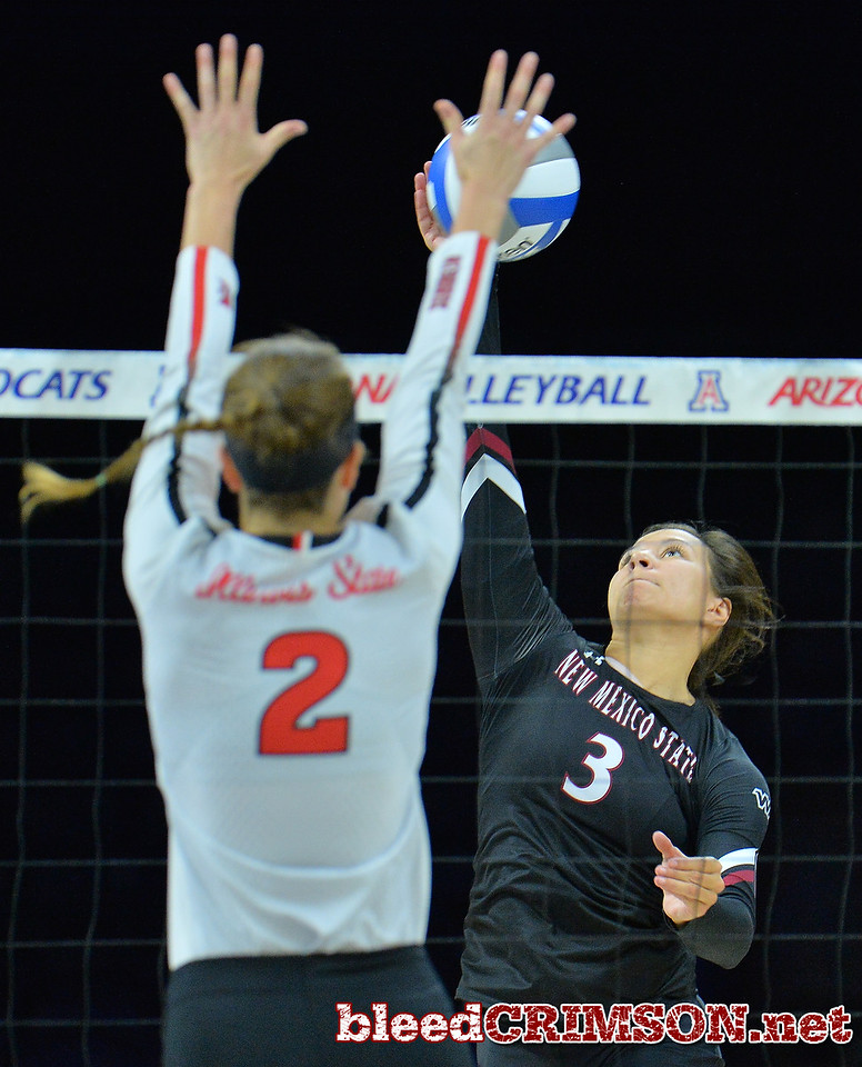 TUCSON, AZ - SEPTEMBER 16:  Jordan Abalos #3 of the New Mexico State Aggies takes a swing against Jaelyn Keene #2 of the Illinois State Redbirds in a match between the New Mexico State Aggies and the Illinois State Redbirds at the McKale Center in Tucson, Arizona. The Redbirds won 3-0.  (Photo by Sam Wasson)