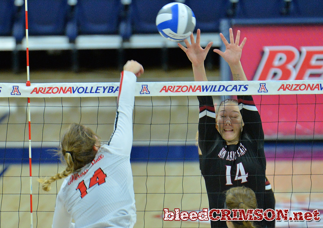 TUCSON, AZ - SEPTEMBER 16:  Kassandra Tohm #14 of the New Mexico State Aggies goes up for a block attempt against Lexi Wallen #14 of the Illinois State Redbirds in a match between the New Mexico State Aggies and the Illinois State Redbirds at the McKale Center in Tucson, Arizona. The Redbirds won 3-0.  (Photo by Sam Wasson)