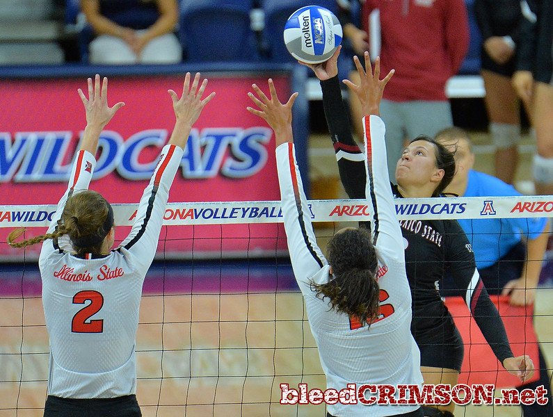 TUCSON, AZ - SEPTEMBER 16:  Jordan Abalos #3 of the New Mexico State Aggies tips a ball over the block attempt of Jaelyn Keene #2 and Lexi Varga #16 of the Illinois State Redbirds in a match between the New Mexico State Aggies and the Illinois State Redbirds at the McKale Center in Tucson, Arizona. The Redbirds won 3-0.  (Photo by Sam Wasson)