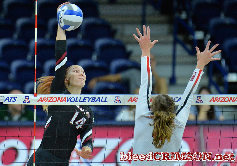 TUCSON, AZ - SEPTEMBER 16:  Kassandra Tohm #14 of the New Mexico State Aggies takes a swing against Stef Jankiewicz #9 of the Illinois State Redbirds in a match between the New Mexico State Aggies and the Illinois State Redbirds at the McKale Center in Tucson, Arizona. The Redbirds won 3-0.  (Photo by Sam Wasson)