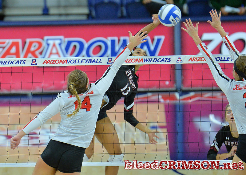 TUCSON, AZ - SEPTEMBER 16:  Brielle Sterns #13 of the New Mexico State Aggies hits a ball between the block attempt of Lexi Wallen #14 and Jaelyn Keene #2 of the Illinois State Redbirds in a match between the New Mexico State Aggies and the Illinois State Redbirds at the McKale Center in Tucson, Arizona. The Redbirds won 3-0.  (Photo by Sam Wasson)