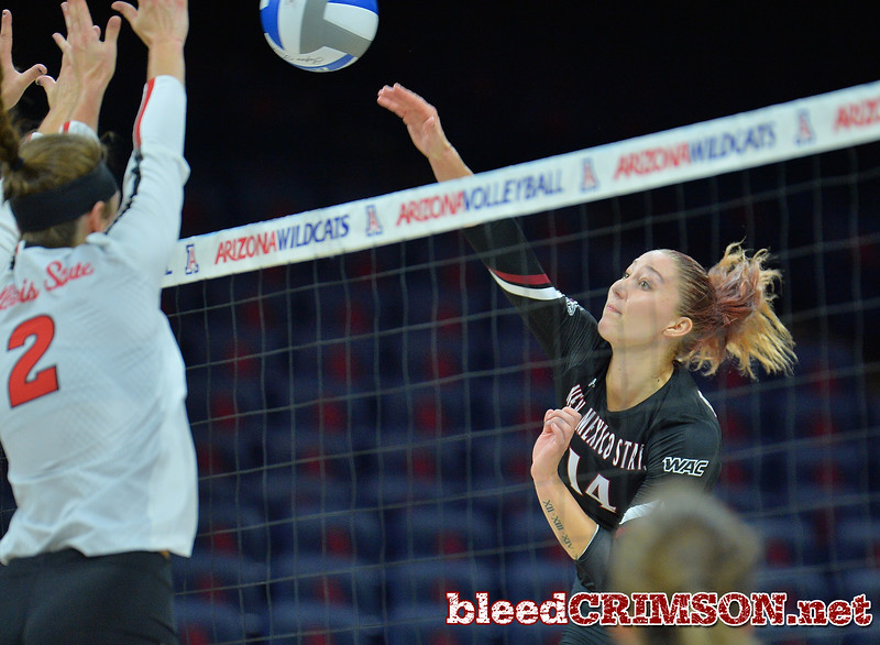 TUCSON, AZ - SEPTEMBER 16:  Kassandra Tohm #14 of the New Mexico State Aggies takes a swing against Jaelyn Keene #2 of the Illinois State Redbirds in a match between the New Mexico State Aggies and the Illinois State Redbirds at the McKale Center in Tucson, Arizona. The Redbirds won 3-0.  (Photo by Sam Wasson)