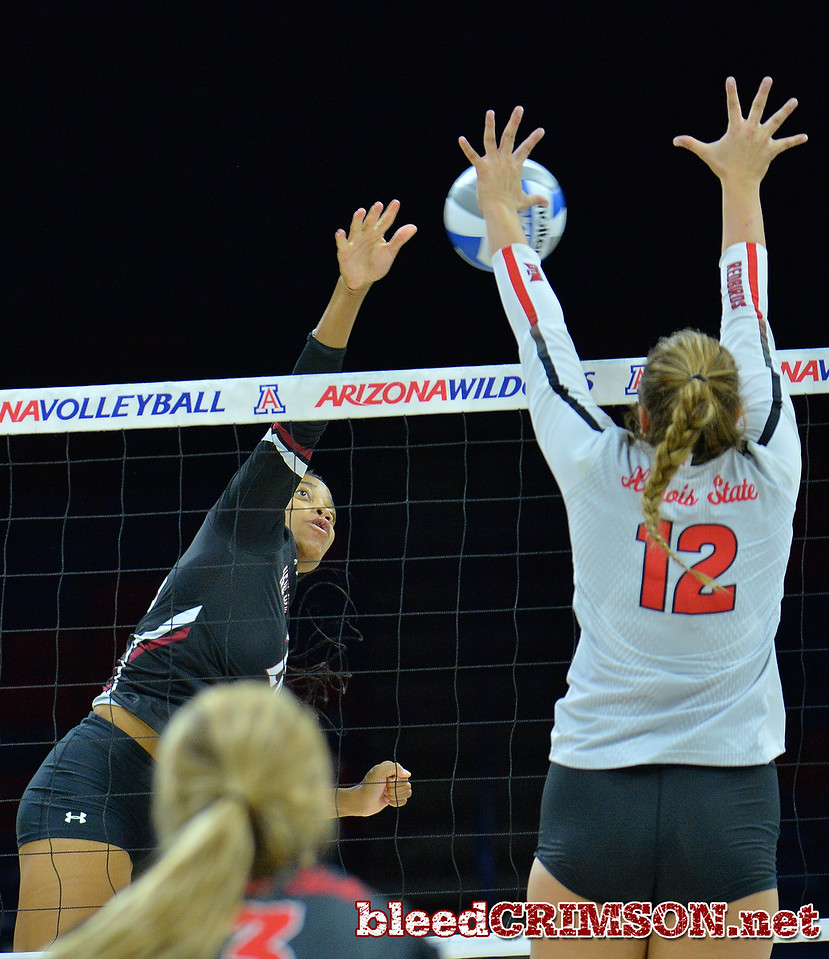 TUCSON, AZ - SEPTEMBER 16:  Sasha-Lee Thomas #20 of the New Mexico State Aggies takes a swing against Machayla Leonard #12 of the Illinois State Redbirds in a match between the New Mexico State Aggies and the Illinois State Redbirds at the McKale Center in Tucson, Arizona. The Redbirds won 3-0.  (Photo by Sam Wasson)