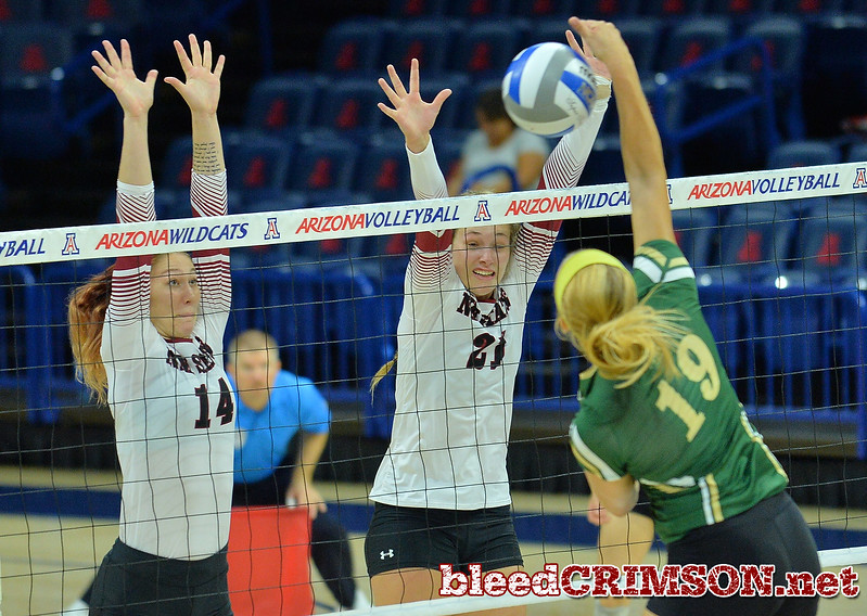 TUCSON, AZ - SEPTEMBER 16:  Kassandra Tohm #14 and Lia Mosher #21 of the New Mexico State Aggies go up for a block attempt against Sydney Biniak #19 of the William & Mary Tribe in a match between the New Mexico State Aggies and the William & Mary Tribe at the McKale Center in Tucson, Arizona. The Aggies won 3-0.  (Photo by Sam Wasson)