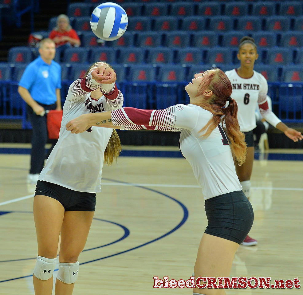 TUCSON, AZ - SEPTEMBER 16:  Briana Ainsworth #1 and Kassandra Tohm #14 of the New Mexico State Aggies try to dig a ball in a match between the New Mexico State Aggies and the William & Mary Tribe at the McKale Center in Tucson, Arizona. The Aggies won 3-0.  (Photo by Sam Wasson)