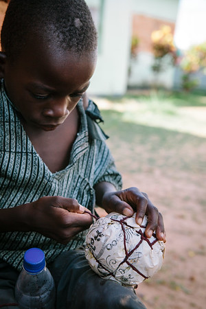 Young boy makes his own ball.  Stringing the ball evenly and tightly makes a big difference.