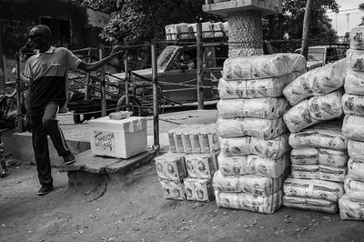 A man selling soda next to a load of flour and rice that will be taken to Venezuela. Behind, a car moving containers with gasoline smuggled. Puerto Santander, Colombia. Photo: Dany Krom.