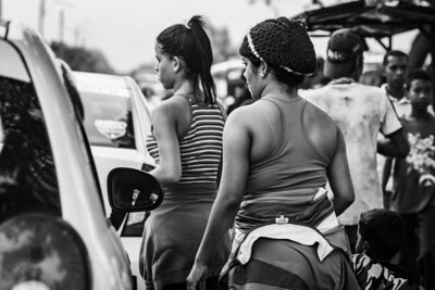 Women walk among the cars that arrive at the La Parada border crossing, offering their services. Cúcuta, Colombia. Photo: Dany Krom.