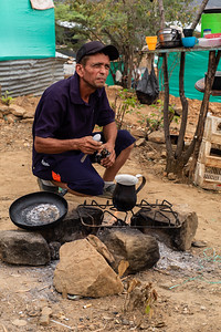 "A man preparing coffe. In the invasions ""Brisas de Paz y Futuro"" and ""Alfonso Gómez"" live around 300 Venezuelan families who occupy these lands illegally where they build their houses of materials that they get at very low cost."