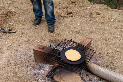 "A man cooking an arepa. The invasions ""Brisas de Paz y Futuro"" and ""Alfonso Gómez"" live around 300 Venezuelan families who occupy these lands illegally where they build their houses of materials that they get at very low cost."