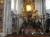 """El Altar de la Cátedra es una de las obras maestras escultóricas de Bernini. En la parte interna de la ventana ovalada, cerrada por una lámina de alabastro con rayos que dividen la superficie en doce sectores como los doce Apóstoles, se encuentra la paloma del Espíritu Santo. A su alrededor se extiende una extraordinaria nube de ángeles y """"putti"""" que coronan la Cátedra en bronce de san Pedro."""