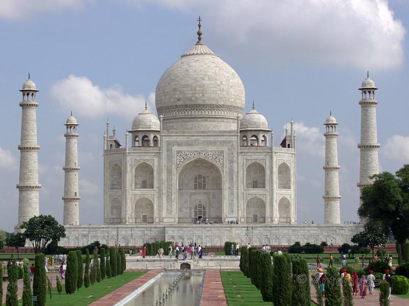 El Taj Mahal es un complejo de edificios construido entre 1631 y 1654 en la ciudad de Agra, India, a orillas del río Yamuna, por el emperador musulmán Sha Jahan de la dinastía mogol. El imponente conjunto se erigió en honor de su esposa favorita, Arjumand Bano Begum — más conocida como Mumtaz Mahal—, quien murió dando a luz a su 14º hijo, y se estima que la construcción demandó el esfuerzo de unos 20.000 obreros.