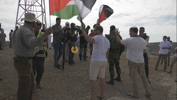 Protesters confront Israeli soldiers during a demonstration by Palestinian land-owners against confiscation of lands by Israel