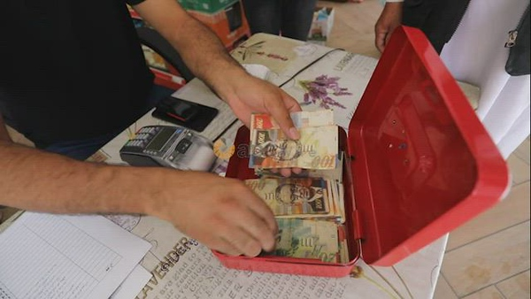 Palestinians receive cash as the United Nations begins to distribute cash aid, funded by Qatar, to thousands of poor families