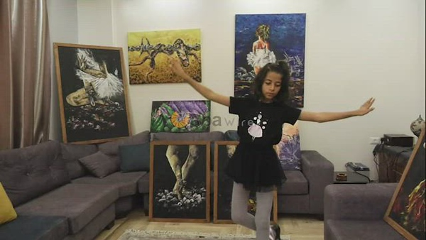 Palestinian artist Abeer Jibril's daughter dances ballet while Abeer Jibril is painting at home