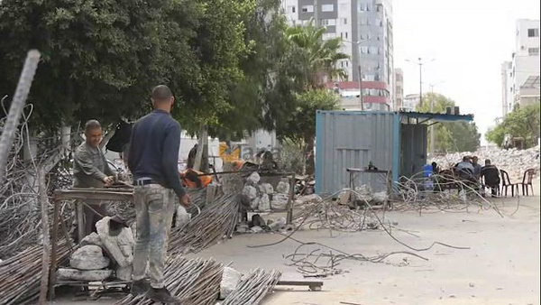 Palestinian workers recycle steel bars from Al-Jawhara Tower which was collapsed early today, after it hit by Israeli air strikes during the recent 11-day conflict between Israel and Hamas on May
