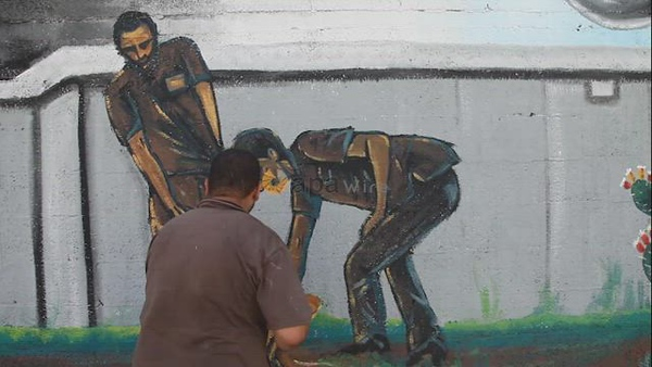 Palestinian artists paint on a mural glorifying six prisoners who escaped from Israel's Gilboa prison almost two weeks ago
